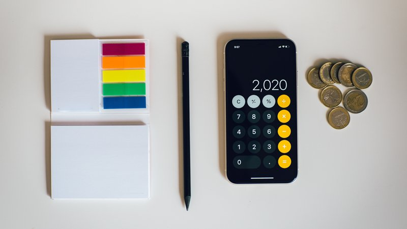 office supplies and coins on white table